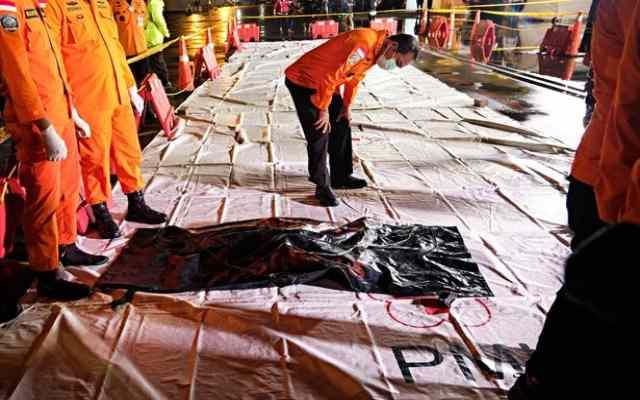 Des secouristes trouvent des parties d'un cadavre après le crash d'un avion de ligne indonésien